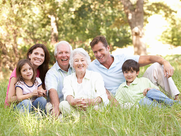A family of four sitting on the grass in a park while smiling and hugging