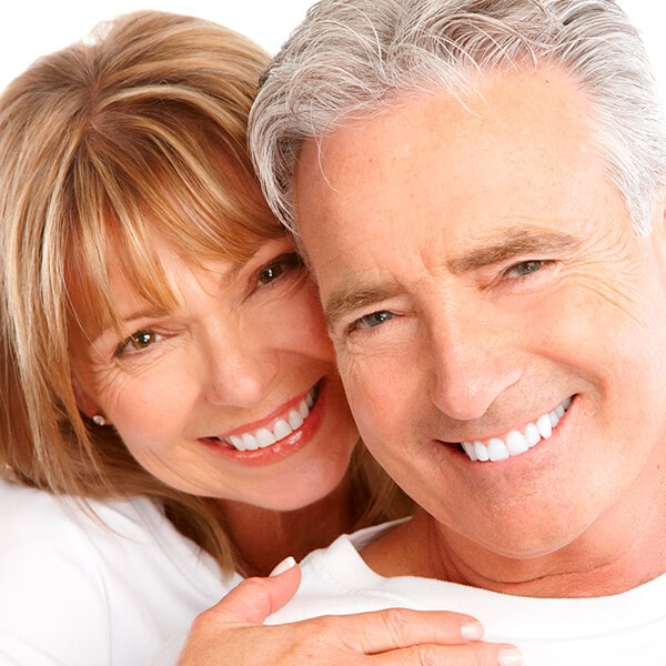 A mature couple hugging each other and smiling with white dentures