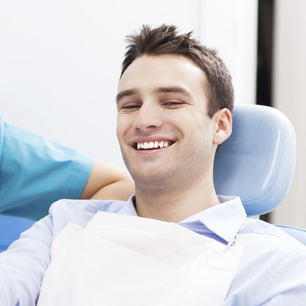Young man sitting in a blue dental treatment chair visiting his dentist for restorative treatment