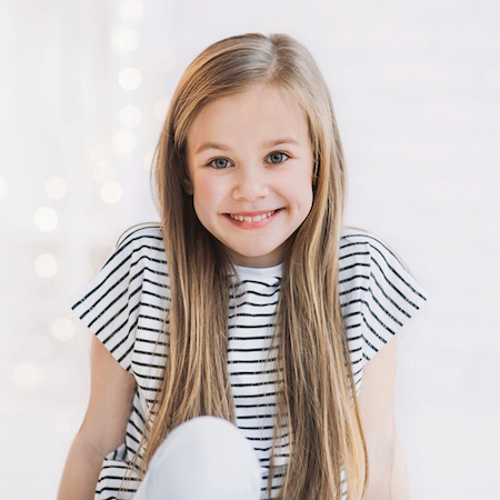 A young girl with long hair and a striped top ready to visit the dentist