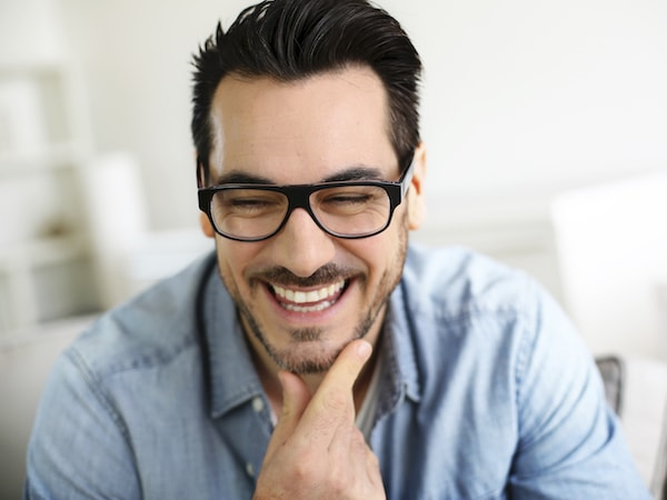 Man with dark hair and glasses resting his chin in his hand and smiling with a blurry background