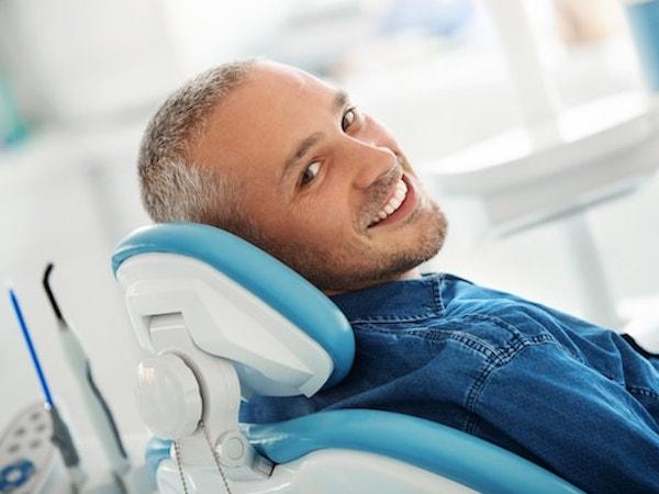 Man in a denim shirt reclining in a dental chair