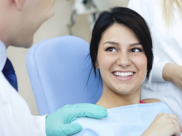 Woman sitting in dental chair as she is about to choose from our services