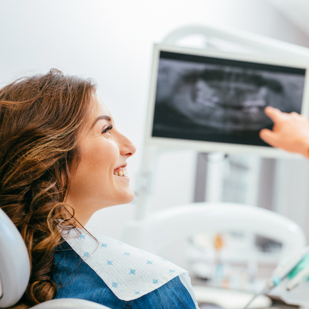 Side profile of a woman in a dental chair and a x-ray screen behind her