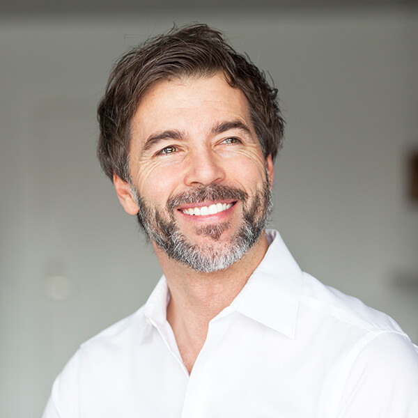 A mature man with white shirt, beard, and black hair ready for his restorative dental implant