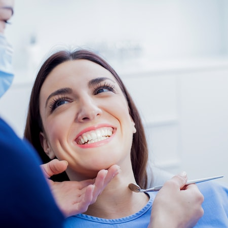A close up of a woman in a dental chair receiving an oral cancer screening