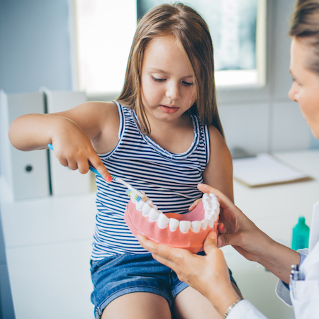 A young girl being shown how to brush teeth as part a family dentistry visit