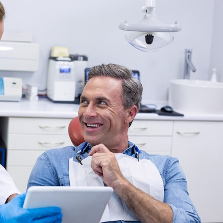 A man looking to his right smiling during a visit to the family dentist