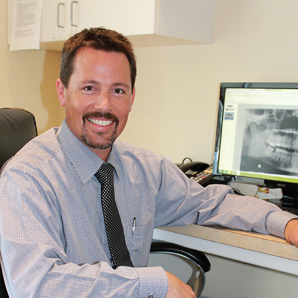 Dr. Romberg addressing a patient in his office with dental x-rays on the monitor