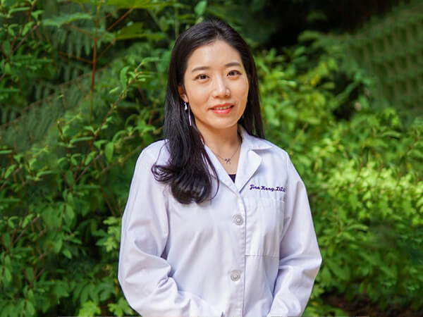One of our lead Bonney Lake dentists, Dr. Kang wearing white scrubs