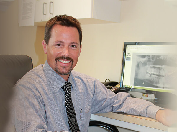 Our Bonney Lake Family Dentist, Dr. Brent Romberg, smiling at his desk